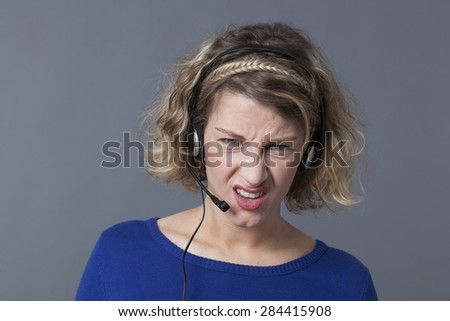 displeased young female professional working for a call center - stock photo