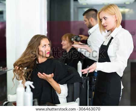 Displeased young girl has a serious conversation with the hairdresser - stock photo