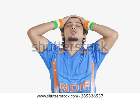 Displeased young man in Indian cricket team jersey standing with hands on head over white background