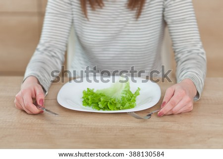 Displeased young woman eating green leaf lettuce. Shallow depth of field, focus on foreground - stock photo