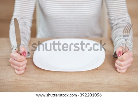 Displeased young woman sitting at the empty plate.
