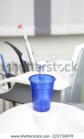 Disposable blue cup in dentist's office - stock photo