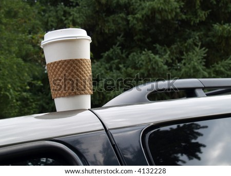 disposable coffee cup left on top of a vehicle - stock photo