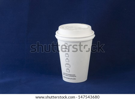 Disposable coffee cup on blue background - stock photo