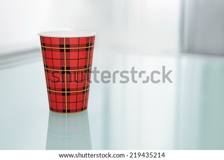 Disposable coffee cup on the glass table.