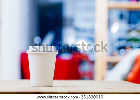 Disposable coffee cup on work table. - stock photo