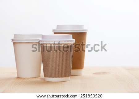 Disposable coffee cups on wooden table. - stock photo