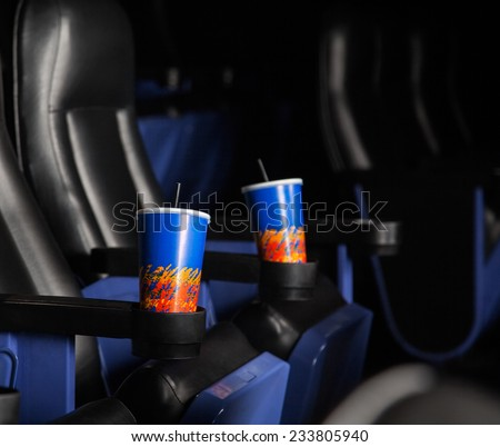Disposable cold drink glasses in armrests of seats at cinema theater - stock photo