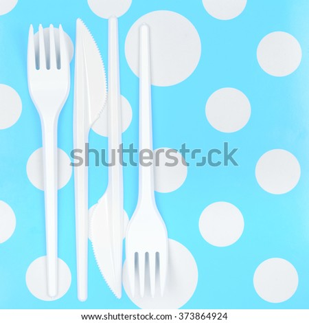 Disposable cutlery: white plastic forks and knifes on bright blue polka dot background. Top view point. - stock photo