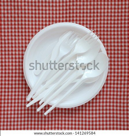 Disposable plastic plate on a checkered cloth. - stock photo