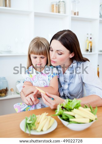 Dissatisfied little girl eating vegetables with her mother in the kitchen