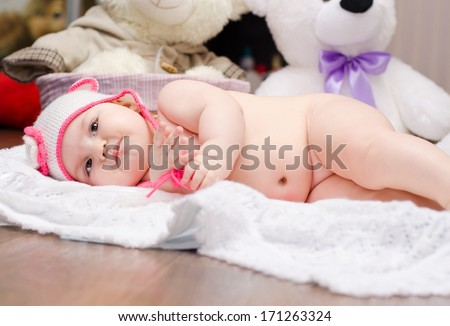 dissatisfied naked baby girl lying in a knitted cap