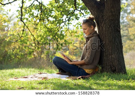Distance education. Young woman sitting near from tree and working with tablet. - stock photo
