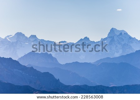 Distant blue toned mountain range of the majestic Ecrins Massif National Park, France, arising higher than 4000 m altitude. - stock photo
