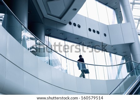 Distant businessman walking in modern office building - stock photo