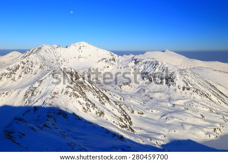 Distant mountain peaks covered with snow in sunny day - stock photo