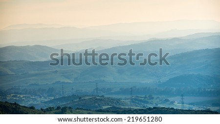 Distant mountain range and thin layer of clouds on the valleys - stock photo