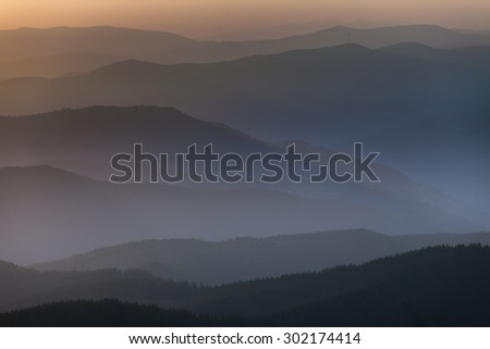 Distant mountain range and thin layer of clouds on the valleys, Ukraine - stock photo