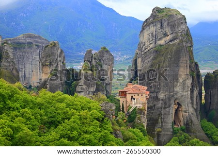 Distant Orthodox monastery surrounded by tall cliffs, Meteora, Greece - stock photo