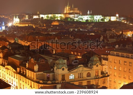 Distant Prague castle and Old Town rooftops illuminated in autumn night, Prague, Czech Republic - stock photo