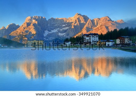 Distant range of Sorapis Mountains and the mirror image created by Misurina lake, Dolomite Alps, Italy - stock photo