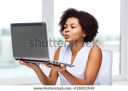 distant relationship, online communication and love concept - happy young african american woman sending kiss to laptop computer