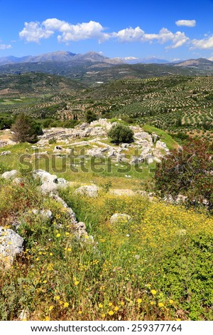Distant ruins of Mycenae located between the green hills of Peloponnese, Greece