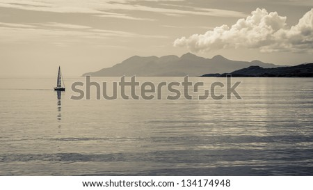 Distant sailboat on calm waters with mountains in the distance.  Black and white toned - stock photo