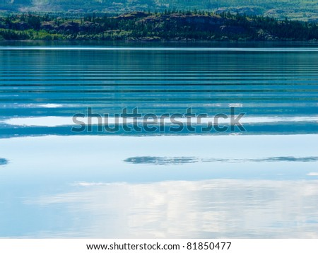 Distant shoreline, clouds and blue sky mirrored on calm lake surface with distortions of some ripples. - stock photo