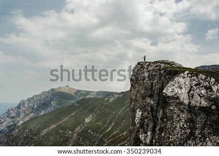 Distant silhouette of a person standing on a rocky mountain cliff and pointing towards the spectacular mountain scenery that lies below.