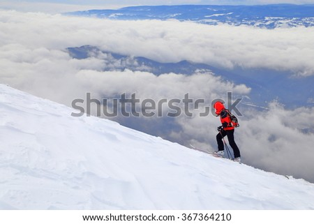 Distant ski mountaineer on steep climb above the clouds - stock photo
