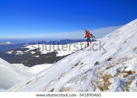 Distant skier carrying skis on the backpack and descending steep ridge in winter - stock photo