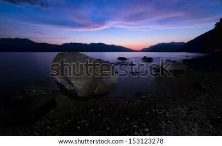Distant sunset at night with large rock along lake. - stock photo