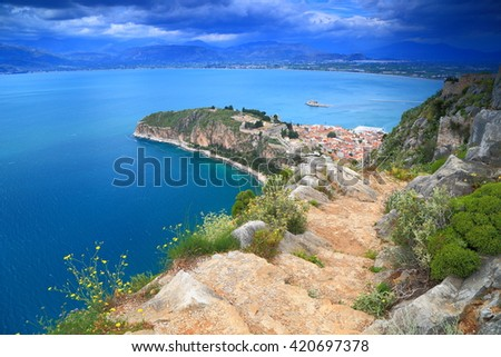 Distant town of Nafplio surrounded by sea in overcast day, Greece
