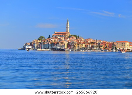 Distant town of Rovinj with tall Venetian church surrounded by the Adriatic sea, Croatia - stock photo