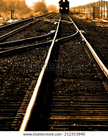 Distant train travelling fast on tracks with lights - stock photo