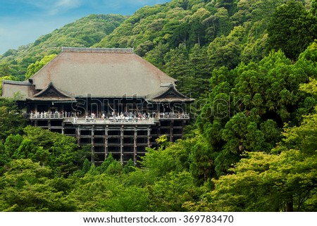 Distant view of Kiyomizu-dera temple nestled in green forest crowded with throngs of tourist visitors on a clear blue sky day in Kyoto, Japan