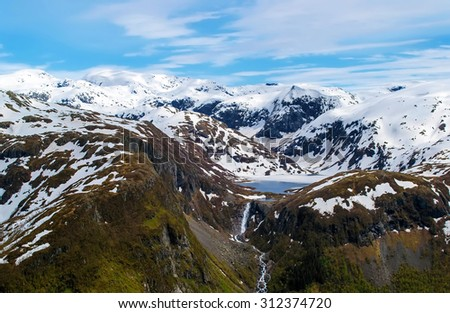 Distant view of the lake from which a waterfall flows, between snow-capped mountain range with steep slopes. Spring. Snow melts. Blue sky. National park Folgefonna. Rosendal,  Norway. - stock photo
