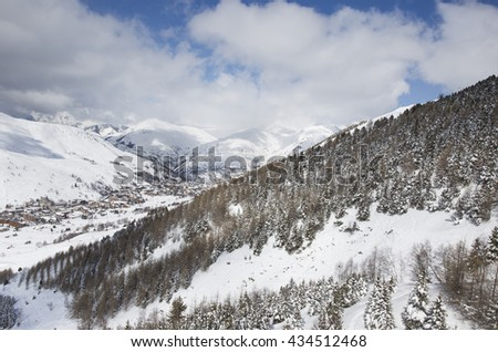 Distant view of the village and ski resort of Les Deux Alpes village, France in the Alps in Europe with alpine trees in the foreground. - stock photo
