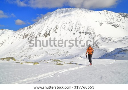 Distant woman on touring skis traversing easy slope across snowy plateau