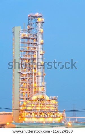 Distillation tower at Oil Refinery Plant at dusk - stock photo