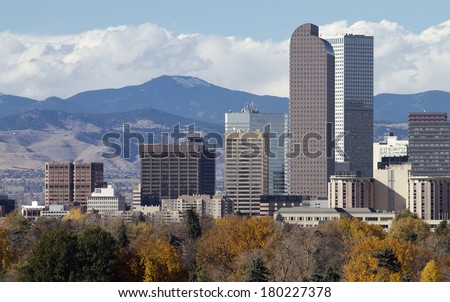 Distinctive Denver, Colorado skyscrapers, with the Rocky Mountains in the background and autumn trees in the foreground. - stock photo
