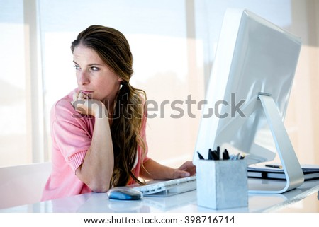 distracted business woman sitting at her desk, looking away from her computer