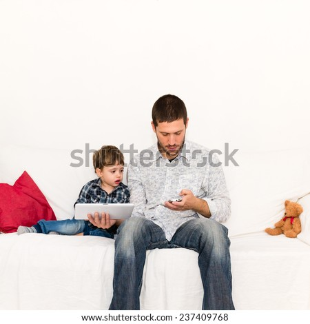 Distracted father making a phone call and playing with tablet with his son sitting on the sofa - stock photo
