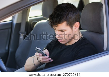 Distracted Handsome Young Man Busy with his Cell Phone While Driving a Car. - stock photo