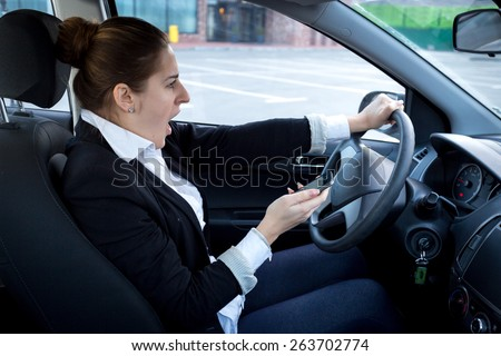 Distracted woman using smartphone while driving a car