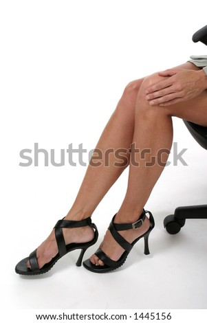 Distractive, sexy legs of executive business woman sitting in office chair. Portrait on white.
