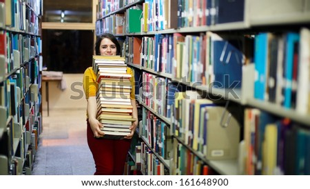 Distressed female student wandering between shelves, searching for books - stock photo