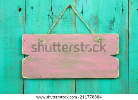 Distressed pink blank sign hanging on antique green rustic wooden fence - stock photo