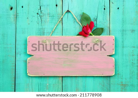 Distressed pink blank sign with red rose bud hanging on antique green wood background - stock photo